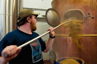 Lucas Dewell removing spent grain from a tank after the brewing process