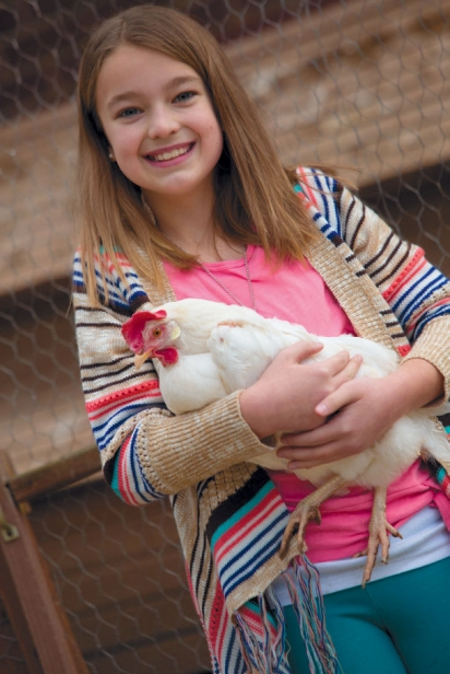 Girl with white chicken in backyard